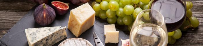 Käseplatte mit Rotwein, Weißwein und Trauben
